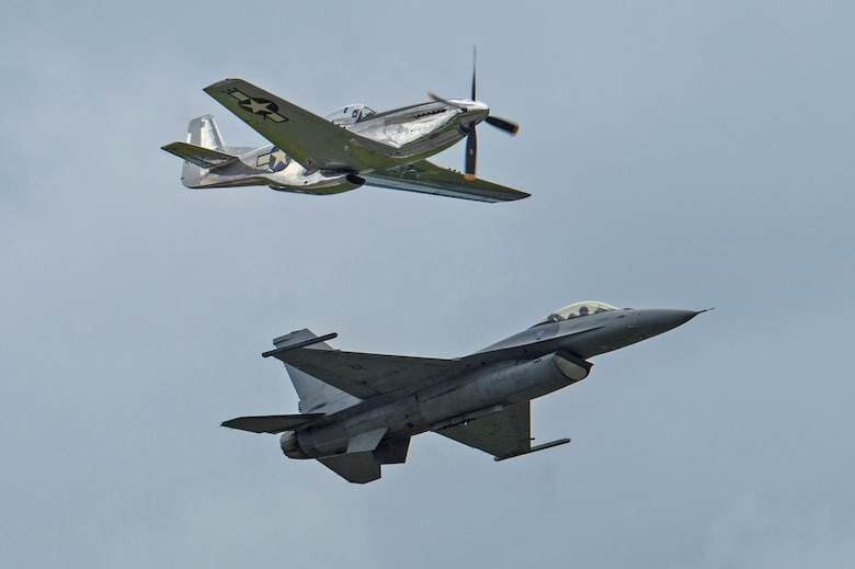 A P-51 Mustang flies above an F-16CM Fighting Falcon during a Heritage Flight performance at the New York Air Show at Stewart International Airport, N.Y., July 1, 2017. The 20th Fighter Wing, created July 28, 1947, began its journey flying P-51D Mustangs and currently flies F-16CM Fighting Falcons, providing combat-ready F-16 airpower and suppression of enemy air defenses. (U.S. Air Force photo by Airman 1st Class Sean Sweeney)