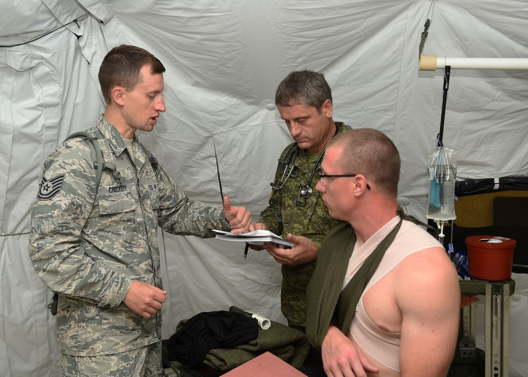 Tech. Sgt. Davy Crockett, 132d Medical Group nursing NCOIC, reviews patient notes with Maj. Enver Bequiri, a doctor in the Kosovo Security Force, July 24, 2017, at Camp Dodge in Johnston, Iowa. Soldiers and Airmen trained together with medics from Kosovo, Iowa's state partner, as well as the United Kingdom. (U.S. Air National Guard photo by Staff Sgt. Michael J. Kelly)