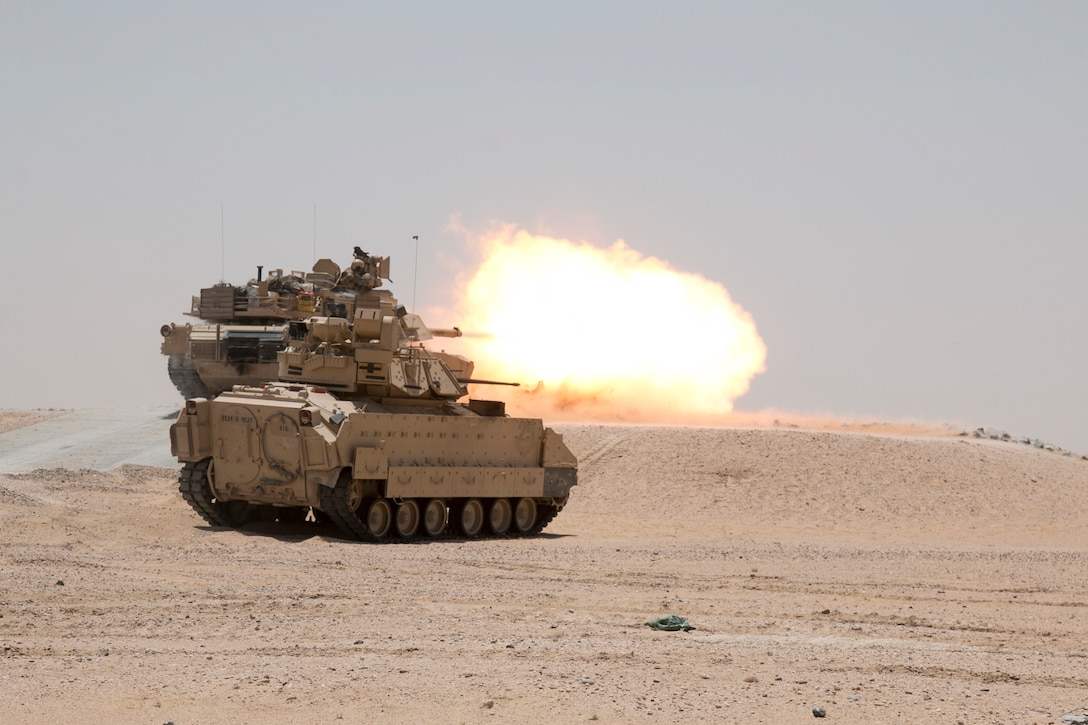 An M1A2 Abrams Main Battle Tank crew engages targets while providing direct fire support for a reconnaissance element during Hunter-Killer training at the Kuwait Multipurpose Range Complex June 7. Saber Squadron is developing Hunter-Killer as a concept, teaming Bradleys up with tanks for increased firepower and speed in the reconnaissance mission. (U.S. Army photo by Staff Sgt. Leah R. Kilpatrick/released)