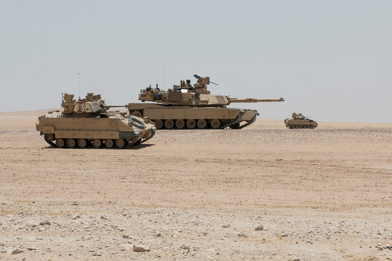 """An M2A3 Bradley armored reconnaissance crew assigned to 6th Squadron, 9th Cavalry Regiment """"Saber,"""" 3rd Armored Brigade Combat Team, 1st Cavalry Division scans the terrain for """"enemy"""" targets while an M1A2 Abrams Main Battle Tank crew provides direct fire support for the reconnaissance element during Hunter-Killer training at the Kuwait Multipurpose Range Complex June 7. Saber Squadron is developing Hunter-Killer as a concept, teaming Bradleys up with tanks for increased firepower and speed in the reconnaissance mission. (U.S. Army photo by Staff Sgt. Leah R. Kilpatrick/released)"""