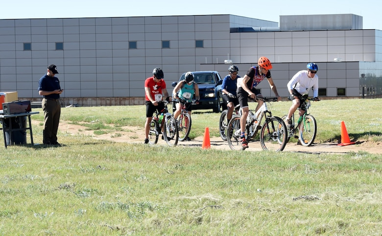 Riders take off for the mountain bike portion of the Tri-Wing Triathlon at Schriever Air Force Base, Colorado, Friday, July 21, 2017. Most contestants completed an arduous 23.2 mile course around the perimeter of the base, while others opted for a 12.2 mile course. The triathlon began with a run at the United States Air Force Academy June 3, 2017, a swim at Peterson AFB June 24 and concluded with the bike race at Schriever AFB.