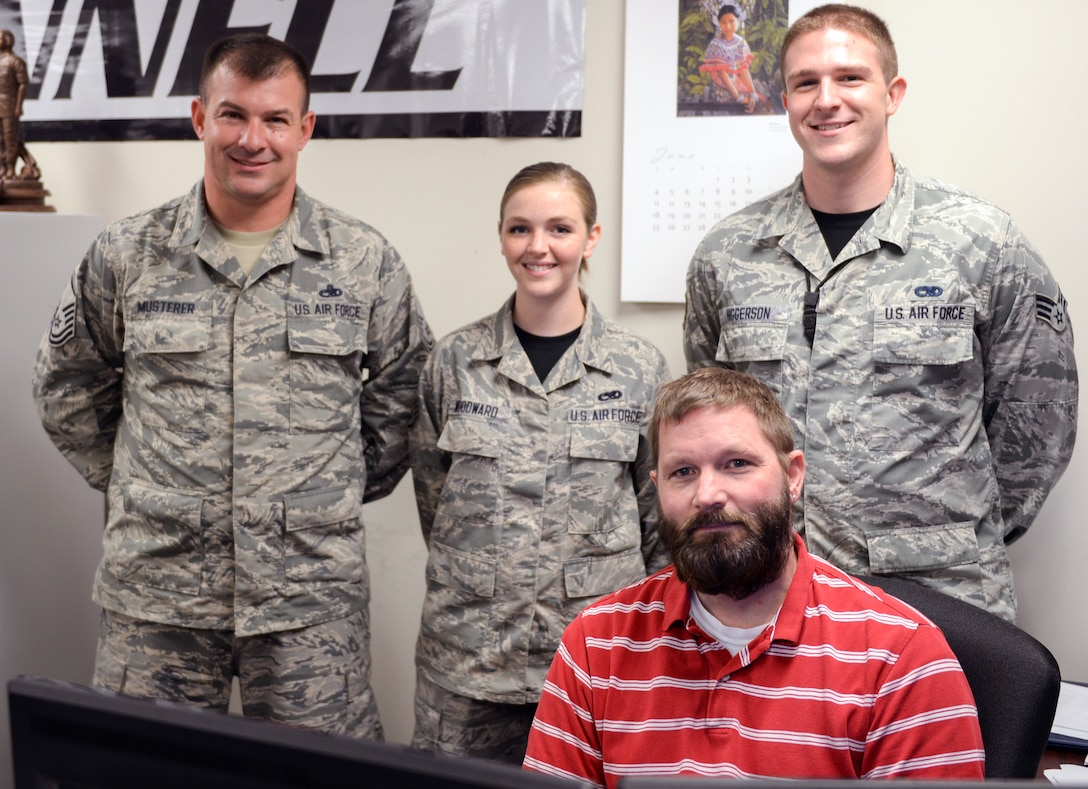 Master Sgt. Edward Musterer, left, 22nd Maintenance Group production superintendent, Staff. Sgt. Chelsa Woodward, right, 22nd Maintenance Operations wing maintenance analyst, and Senior Airman Eric Higgerson, 22nd MXO maintenance scheduler, pose behind Brian Hansen, 22nd MXO engine manager, July 14, 2017, at McConnell Air Force Base, Kan. The Airmen answered Hansen's call for help when he went into cardiac arrest April 20, ultimately saving his life. (U.S. Air Force photo/Senior Airman Colby L. Hardin)