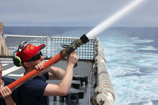 Damage Control Chief David Warner trains shipmates on hose handling techniques.