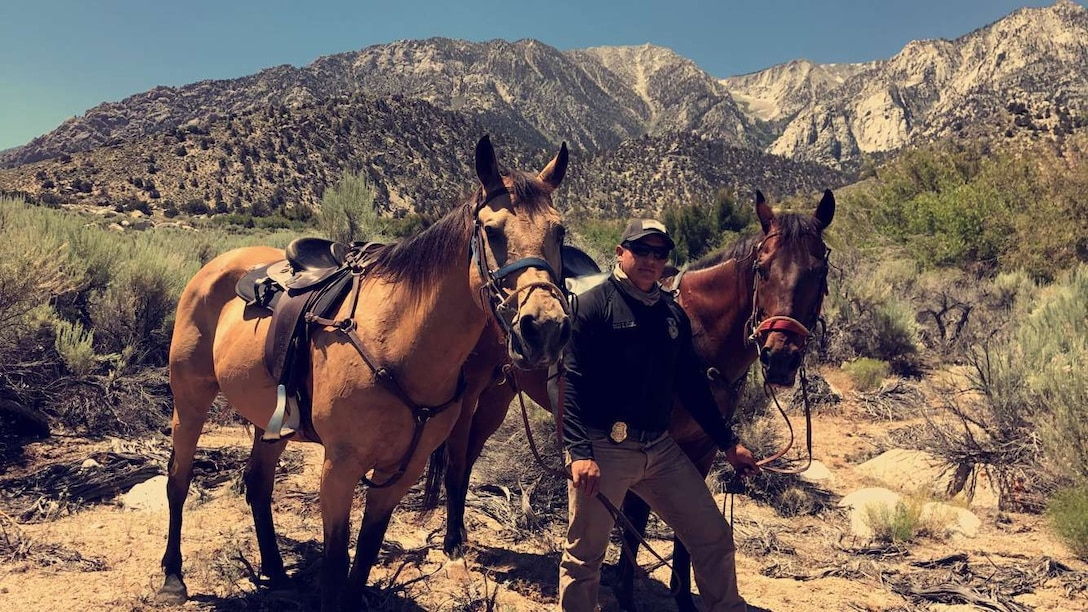 Staff Sgt. Elias Romero, 30th Security Forces Squadron Mounted Horse Patrol NCOIC, takes a photo with Duke, Military Working Horse, and Trooper, Military Working Horse, June 29, 2017, Lone Pine, Calif. The Vandenberg Mounted Horse Patrol was requested nearly a week after a RQ-4 Global Hawk unmanned surveillance aircraft assigned to the 9th Reconnaissance Wing at Beale Air Force Base crashed during a trip back to its home station, June 21. (courtesy photo)