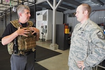 Master Sgt. Steve Hager, 934th Explosive Ordnance Disposal, talks about protective gear to Honorary Commander John Stenz. (Air Force Photo/Paul Zadach)