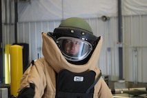 Honorary Commander Brad Ingber tries on a bomb suit. (Air Force Photo/Paul Zadach)