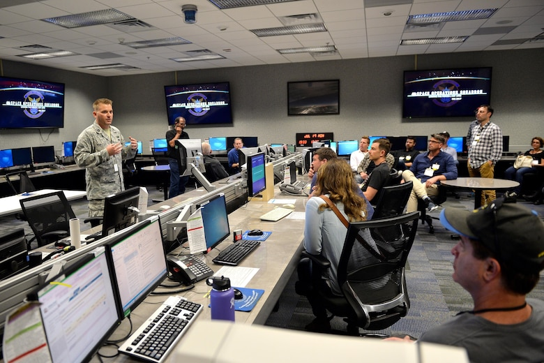 Capt. Paul Karsten (left), 4th Space Operations Squadron deployment commander, briefs Hollywood tour participants on different aspects of the space mission at Schriever Air Force Base, Colorado, July 17, 2017. The Hollywood directors, writers and producers used the tour to gain information of the not only the military, but specifically the Air Force and how they support the space mission. (U.S. Air Force photo/Dennis Rogers)