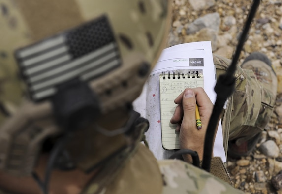 A joint terminal attack controller writes coordinates on a notebook during a training exercise on the Nevada Test and Training Range July 19, 2017. The JTACs worked with A-10 Thunderbolt II attack aircraft to accomplish live-fire training. (U.S. Air Force photo by Senior Airman Kevin Tanenbaum/Released)