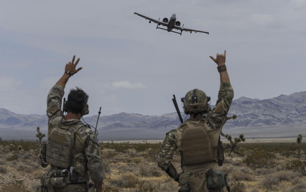 Joint terminal attack controllers wave at an A-10 Thunderbolt II attack aircraft during a show of force on the Nevada Test and Training Range July 19, 2017. The A-10 has excellent maneuverability at low air speeds and low-altitude, and is a highly accurate weapons delivery platform. (U.S. Air Force photo by Senior Airman Kevin Tanenbaum/Released)