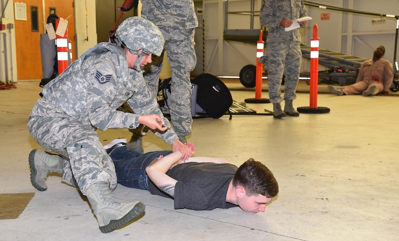 Staff Sgt. Hali Klein, 45th Security Forces Squadron, apprehends a suspect during a joint 920th Rescue Wing and 45th Space Wing active shooter exercise July 25, 2017 in Hangar 750. During the scenario, four Airmen were wounded and three Airmen were killed by a military assailant. The security forces team was the first to respond to the scene, followed by a team of 308th Rescue Squadron pararesceumen and 45th Civil Engineer Squadron firefighters. (U.S. Air Force photo/Tech. Sgt. Lindsey Maurice)