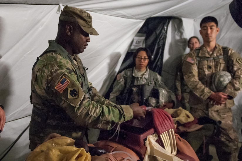 """U.S. Army Reserve Sgt. 1st Class Terry Warren, of the Effects and Enablers Team augmenting the 84th Training Command Combat Support Training Exercise and the Army Medical Command's Global Medic Exercise headquartered out of Fort Hunter Liggett, California, demonstrates a """"cut suit."""" This surgical suit is meant to replicate realistic scenarios for medical professionals to train on during mass casualty exercises on Camp Roberts, California, July 16, 2017. (U.S. Army Reserve Photo by Spc. Ce Shi, 222nd Broadcast Public Affairs Detachment)"""