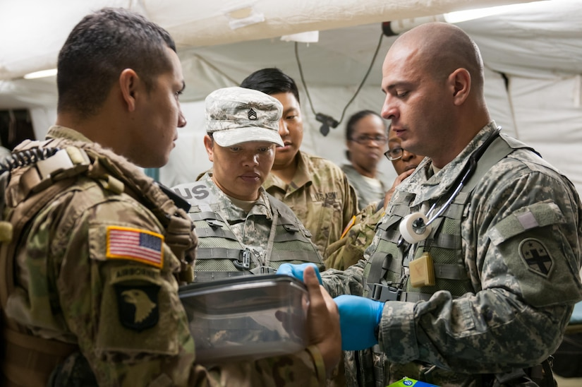 U.S. Army Reserve Sgt. Daniel Ledezma, at right, a combat medic with the 331st Minimal Care Detachment in Miami, hands simulated lab results to a fellow medic at the 47th Combat Support Hospital on Camp Roberts, California, July 17, 2017. The CSH is part of the 84th Training Command's Combat Support Training Exercise and the Army Medical Command's Global Medic Exercise headquartered out of Fort Hunter Liggett, California. (U.S. Army Reserve photo by Spc. Miguel Alvarez, 354th Mobile Public Affairs Detachment)
