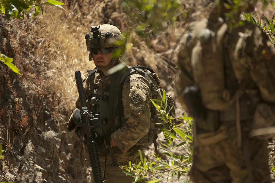 Pfc. Austin Broadway watches for opposing forces soldiers while maneuvering to an observation post near the 718th Engineer Company's motor pool during training on Fort Hunter Liggett, Calif., on July 19, 2017. Broadwell cuffed his sleeves to help stay cool as part of an approved plan to let the Soldiers work in heat category 5. The 718th is an Army Early Response Force unit, capable of deploying within 30 days of notification to support any combatant command in the world. Nearly 5,400 service members from the U.S. Army Reserve Command, U.S. Army, Army National Guard, U.S. Navy, and Canadian Armed Forces are training at Fort Hunter Liggett as part of the 84th Training Command's CSTX 91-17- 03 and ARMEDCOM's Global Medic; this is a unique training opportunity that allows U.S. Army Reserve units to train alongside their multi-component and joint partners as part of the America's Army Reserve evolution into the most lethal Federal Reserve force in the history of the nation. (U.S. Army Reserve photo by Sgt. David L. Nye, 301st Public Affairs Detachment)