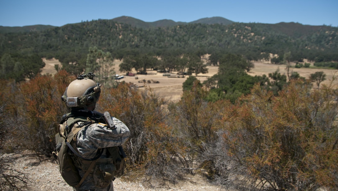 Sgt. Shawn Crampes, a noncommissioned officer with the 718th Engineer Company, watches the main approaches to his company's motor pool and command post while stationed on a nearby hill on July 19, 2017, at Fort Hunter Liggett, Calif. The observation post was part of the company's security plan to allow them to safely build and improve their base of operations while under threat of simulated attack. Nearly 5,400 service members from the U.S. Army Reserve Command, U.S. Army, Army National Guard, U.S. Navy, and Canadian Armed Forces are training at Fort Hunter Liggett as part of the 84th Training Command's CSTX 91-17- 03 and ARMEDCOM's Global Medic; this is a unique training opportunity that allows U.S. Army Reserve units to train alongside their multi-component and joint partners as part of the America's Army Reserve evolution into the most lethal Federal Reserve force in the history of the nation. (U.S. Army Reserve photo by Sgt. David L. Nye, 301st Public Affairs Detachment)