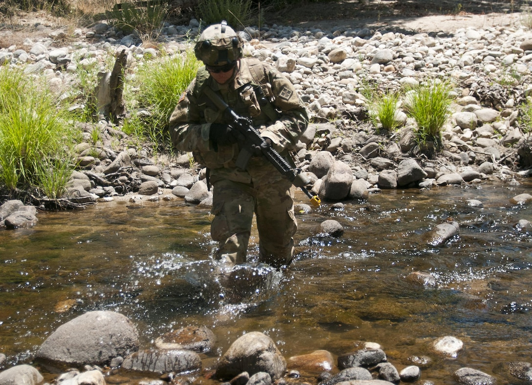 Pfc. Austin Broadway crosses a stream while maneuvering to an observation post near the 718th Engineer Company's command post during training on Fort Hunter Liggett, Calif., on July 19, 2017. The 718th is an Army Early Response Force unit, capable of deploying within 30 days of notification to support any combatant command in the world. Nearly 5,400 service members from the U.S. Army Reserve Command, U.S. Army, Army National Guard, U.S. Navy, and Canadian Armed Forces are training at Fort Hunter Liggett as part of the 84th Training Command's CSTX 91-17-03 and ARMEDCOM's Global Medic; this is a unique training opportunity that allows U.S. Army Reserve units to train alongside their multi-component and joint partners as part of the America's Army Reserve evolution into the most lethal Federal Reserve force in the history of the nation. (U.S. Army Reserve photo by Sgt. David L. Nye, 301st Public Affairs Detachment)