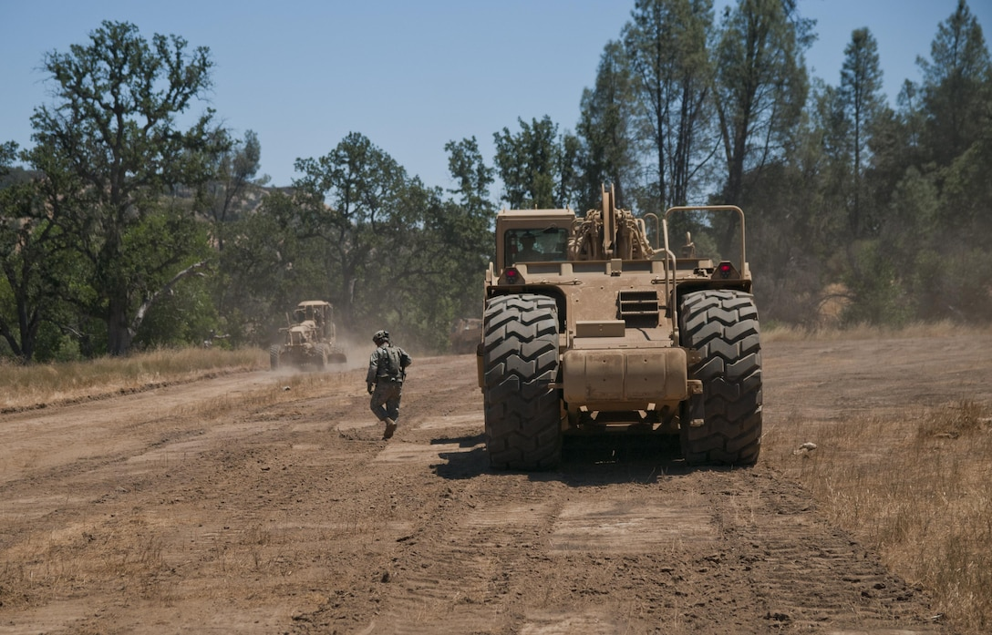 Sgt. Robert Burns, a squad leader with the 718th Engineer Company, moves from speaking with the driver of a scraper to the driver of a grader. Burns was acting as the platoon leader after the actual platoon leader was notionally eliminated in combat with opposing forces. Nearly 5,400 service members from the U.S. Army Reserve Command, U.S. Army, Army National Guard, U.S. Navy, and Canadian Armed Forces are training at Fort Hunter Liggett as part of the 84th Training Command's CSTX 91-17- 03 and ARMEDCOM's Global Medic; this is a unique training opportunity that allows U.S. Army Reserve units to train alongside their multicomponent and joint partners as part of the America's Army Reserve evolution into the most lethal Federal Reserve force in the history of the nation. (U.S. Army Reserve photo by Sgt. David L. Nye, 301st Public Affairs Detachment)