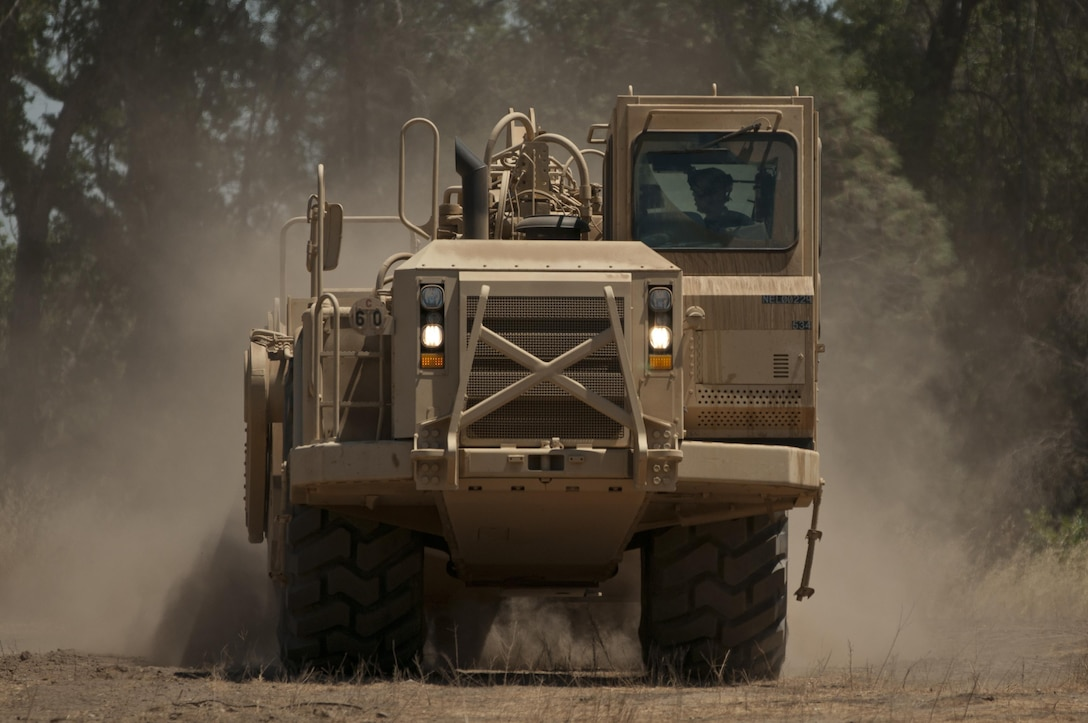 Spc. Dylan Sugg, a horizontal engineer with the 718th Engineer Company, scrapes the terrain of the company's temporary motor pool at Fort Hunter Liggett, Calif., during training on July 19, 2017. The scraper allowed the Soldier to get the motor pool more level to ease loading and unloading operations, but it also protected him from potential small arms fire from opposing forces in the training. Nearly 5,400 service members from the U.S. Army Reserve Command, U.S. Army, Army National Guard, U.S. Navy, and Canadian Armed Forces are training at Fort Hunter Liggett as part of the 84th Training Command's CSTX 91-17- 03 and ARMEDCOM's Global Medic; this is a unique training opportunity that allows U.S. Army Reserve units to train alongside their multi-component and joint partners as part of the America's Army Reserve evolution into the most lethal Federal Reserve force in the history of the nation. (U.S. Army Reserve photo by Sgt. David L. Nye, 301st Public Affairs Detachment)