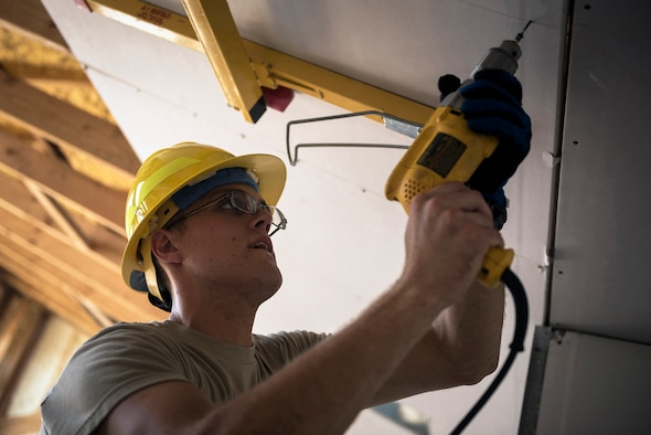U.S. Air Force Staff Sgt. Daniel Kern, an electrical power production specialist with the 182nd Civil Engineer Squadron, Illinois Air National Guard, attaches drywall to the ceiling during annual training in Crow Agency, Mont., July 24, 2017. The squadron helped build homes for Native American veterans as part of the Department of Defense's Innovative Readiness Training civil-military relations program. (U.S. Air National Guard photo by Tech. Sgt. Lealan Buehrer)