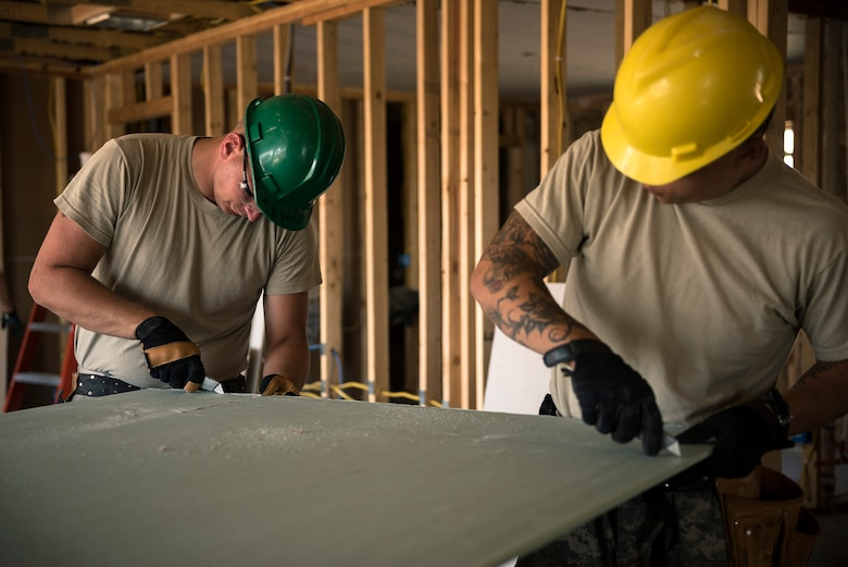 U.S. Army Staff Sgt. Stevn Henke, left, a section sergeant, and Spc. Dan Rose, a concrete and masonry specialist, both with the 230th Vertical Engineer Company, Montana Army National Guard, cut drywall in Crow Agency, Mont., July 24, 2017. The soldiers teamed up with the Illinois Air National Guard's 182nd Civil Engineer Squadron to help build homes for Native American veterans as part of the Department of Defense's Innovative Readiness Training civil-military relations program. (U.S. Air National Guard photo by Tech. Sgt. Lealan Buehrer)