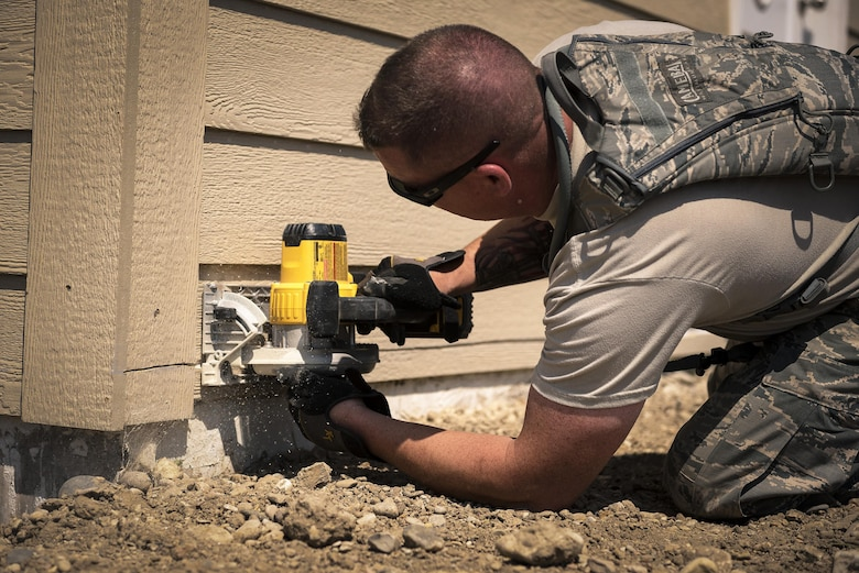 U.S. Air Force Staff Sgt. Christopher Boen, a pavement and construction equipment specialist with the 182nd Civil Engineer Squadron, Illinois Air National Guard, trims siding during annual training in Crow Agency, Mont., July 24, 2017. The squadron helped build homes for Native American veterans as part of the Department of Defense's Innovative Readiness Training civil-military relations program. (U.S. Air National Guard photo by Tech. Sgt. Lealan Buehrer)