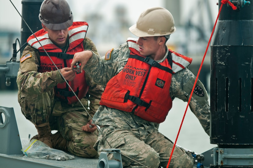 Pfc. Zach Figueroa, a member of the 331st Transportation Company, takes a bolt from Pvt. Michael Grella, also with the 331st, while reassembling a modular warping tug in the Port of San Diego during training on July 16, 2017, in support of an engineering project to construct a causeway. The causeway is used to quickly move supplies from ships to shore. U.S. Army Reserve Command Soldiers are participating in Exercise Big LOTS West, a joint military training exercise designed to reinforce the 1394th Transportation Brigade's ability to rapidly deploy vital combat equipment to an operational environment. (Photo by U.S. Army Reserve Sgt. David L. Nye, 301st Public Affairs Detachment)