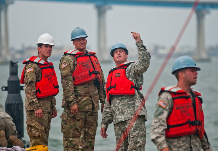 Leaders with the 331st Transportation Company discuss crane movements on a pier at the Port of San Diego as their men reassemble an Army modular warping tug, a boat used to control larger vessels, during training at the port on July 16, 2017, in support of an engineering project to construct a causeway. U.S. Army Reserve Command Soldiers are participating in Exercise Big LOTS West, a joint military training exercise designed to reinforce the 1394th Transportation Brigade's ability to rapidly deploy vital combat equipment to an operational environment. (Photo by U.S. Army Reserve Sgt. David L. Nye, 301st Public Affairs Detachment)