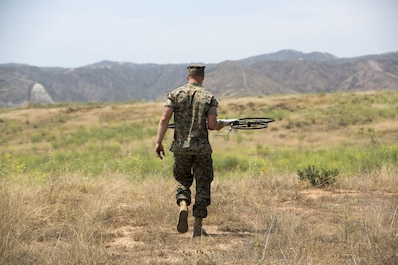 A critical skills operator with 1st Marine Raider Support Battalion, U.S. Marine Corps Forces, Special Operations Command, places the Joint Tactical Aerial Resupply Vehicle (JTARV) at a launch site prior to take off aboard Marine Corps Base Camp Pendleton, Calif., July 7, 2017. The JTARV, which is in the developmental phase, is a lightweight autonomous vehicle which provides an aerial resupply capability for immediate support to operational units. It was being tested as a resupply platform for machine-gun sustainment training with a cargo unmanned logistics system (C-ULS) during a tactical readiness exercise (TRX).