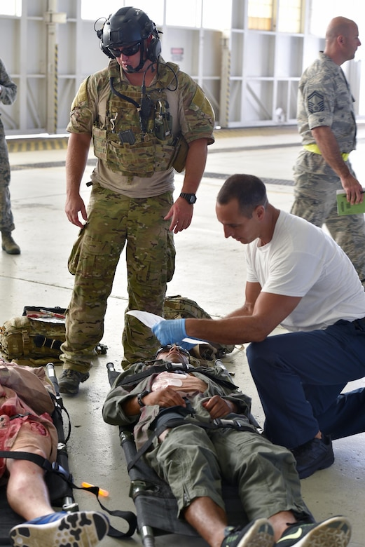 Matthew Martines, right, 45th Civil Engineer Squadron firefighter, receives a status update on a victim of an active shooter exercise, upon arriving on scene from Master Sgt. Louis Hause, 308th Rescue Squadron pararescueman, July 25, 2017 in Hangar 750. Pararescuemen worked closely with installation firefighters to tend to victims on scene and load them into ambulances for transport to the hospital. The joint exercise between the 920th Rescue Wing and 45th Space Wing tested the units' ability to work together in an emergency situation. (U.S. Air Force photo/Tech. Sgt. Lindsey Maurice)