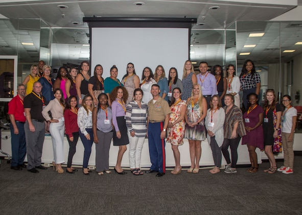 U.S. Marines and spouses with 6th Marine Corps District (6MCD) pose for a group photo during the District Spouse Orientation Course (DSOC) at the Four Winds Family Readiness Center aboard Marine Corps Recruit Depot Parris Island, South Carolina, July 26, 2017.  The DSOC provided Marines and their spouses a broad spectrum of tools to help them transition into the Marine Corps' recruiting field. The spouses came from across the District to build connections and network with fellow spouses.  (U.S. Marine Corps photo by Lance Cpl. Jack A. E. Rigsby)