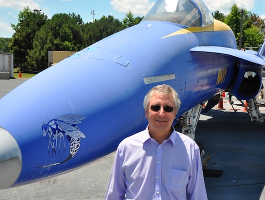 Kurt Mikoleit stands in front of an F-18 that is used as a ground plane for testing and evaluating the hazards of electromagnetic radiation to ordnance at NSWC Dahlgren 