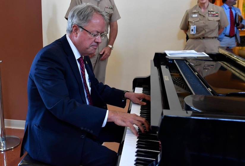 Charleston Mayor John Tecklenburg, plays the piano for Joint Base Charleston leadership during a mission briefing inside the Naval Health Clinic Charleston here, July 25. The locations Tecklenburg toured included Naval Health Clinic Charleston, the Naval Nuclear Power Training Command and the 841st Transportation Battalion. Tecklenburg was selected to represent the installation at the Joint Civilian Orientation Conference in August 2017. The mission of JCOC is to increase public understanding of national defense by enabling American business and community leaders to directly observe and engage with the U.S. military.