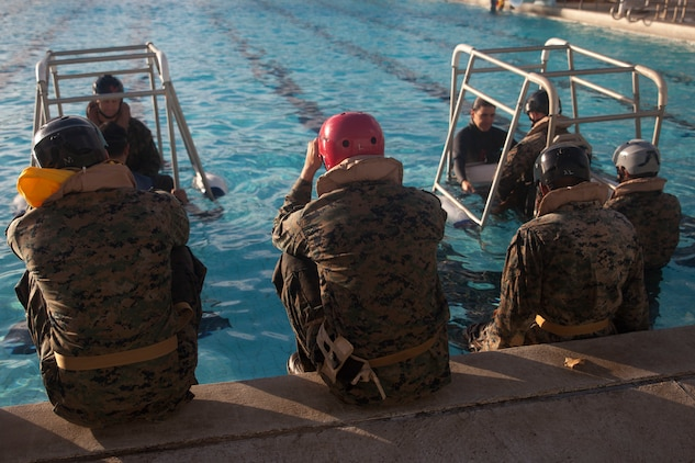 U.S. Marines assigned to 3rd Marine Regiment, 3rd Marine Division, prepare to complete the Shallow Water Egress Training at the base pool aboard Marine Corps Base Hawaii, July 21, 2017. In the event of an Amphibious Assault Vehicle sinking, Submerged Vehicle Egress Training and Underwater Egress Training are vital training programs that prepares Marines and Sailors on safely escaping the vehicle. (U.S. Marine Corps photo by Lance Cpl. Matthew Kirk)
