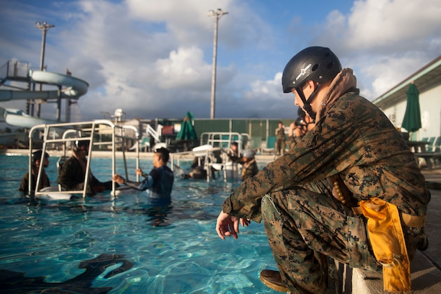 Lance Cpl. Justin Collins, a grenadier with 3rd Marine Regiment, 3rd Marine Division, waits to complete the Shallow Water Egress Training at the base pool aboard Marine Corps Base Hawaii, July 21, 2017. In the event of an Amphibious Assault Vehicle sinking, Submerged Vehicle Egress Training and Underwater Egress Training are vital training programs that prepares Marines and Sailors on safely escaping the vehicle. (U.S. Marine Corps photo by Lance Cpl. Matthew Kirk)