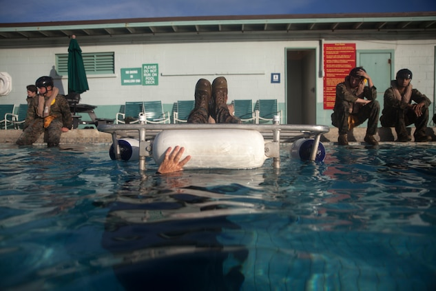 Cpl. Edward Moore, a supply specialist with 3rd Marine Regiment, 3rd Marine Division, is submerged during Shallow Water Egress Training at the base pool aboard Marine Corps Base Hawaii, July 21, 2017. In the event of an Amphibious Assault Vehicle sinking, Submerged Vehicle Egress Training and Underwater Egress Training are vital training programs that prepares Marines and Sailors on safely escaping the vehicle. (U.S. Marine Corps photo by Lance Cpl. Matthew Kirk)