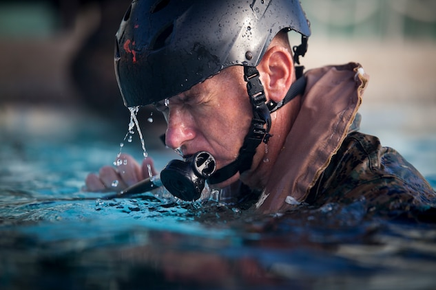 Col. Michael Styskal, the commanding officer of 3rd Marine Regiment, 3rd Marine Division, practices using an Emergency Breathing System during Shallow Water Egress Training, Marine Corps Base Hawaii, July 21, 2017. In the event of an Amphibious Assault Vehicle sinking, Submerged Vehicle Egress Training and Underwater Egress Training are vital training programs that prepares Marines and Sailors on safely escaping the vehicle. (U.S. Marine Corps photo by Lance Cpl. Matthew Kirk)