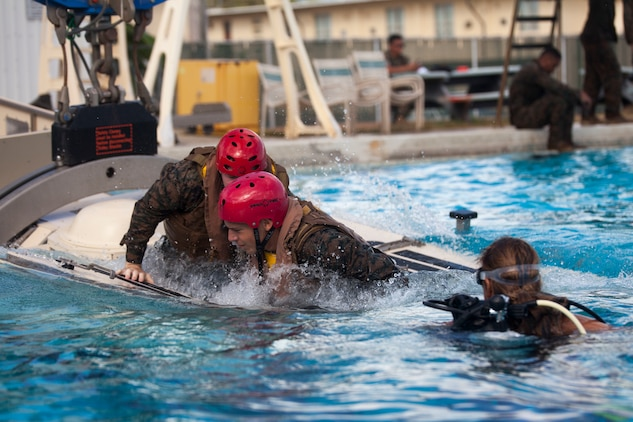 U.S. Marines assigned to 3rd Marine Regiment, 3rd Marine Division, escape a Submerged Vehicle Egress Trainer (SVET) during Underwater Egress Training (UET), Marine Corps Base Hawaii, July 21, 2017. In the event of an Amphibious Assault Vehicle sinking, SVET and UET are vital training programs that prepares Marines and Sailors on safely escaping the vehicle. (U.S. Marine Corps photo by Lance Cpl. Matthew Kirk)