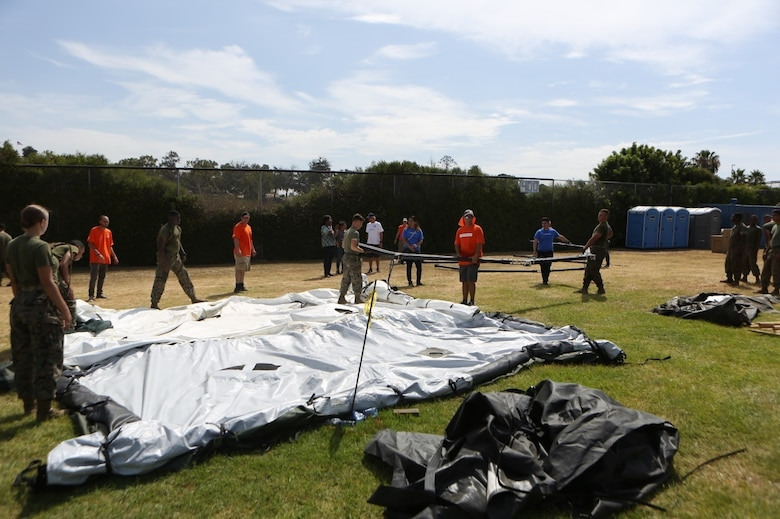Marines with Marine Wing Support Squadron (MWSS) 373 and other volunteers set up tents for the Veterans Village of San Diego's Homeless Veteran Stand Down at San Diego High School in San Diego, July 19. The Veterans Village of San Diego hosted the Homeless Veteran Stand Down to support homeless veterans by giving them a place to stay and providing services such as medical care, dental care, legal assistance, haircuts and food for three days. (U.S. Marine Corps photo by Cpl. Daniel Auvert/ Released)