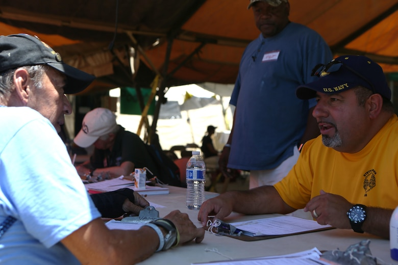 Luis Patino, right, a Navy veteran and volunteer with the Veterans Village of San Diego (VVSD), assists a veteran who is receiving medical care during the 30th Annual Homeless Veteran Stand Down at San Diego High School in San Diego, July 21. VVSD hosted the event July 19 to 21 to support San Diego's homeless veterans by providing services such as medical and dental care, legal assistance, hygiene services, food and shelter during the stand down. (U.S. Marine Corps photo by Cpl. Daniel Auvert/Released)