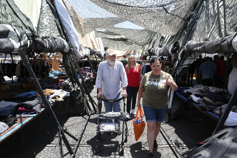 Two volunteers with the Veterans Village of San Diego help a veteran select clothes during the 30th Annual Homeless Veteran Stand Down at San Diego High School in San Diego, July 21. VVSD hosted the event July 19 to 21 to support San Diego's homeless veterans by providing services such as medical and dental care, legal assistance, hygiene services, food and shelter during the stand down. (U.S. Marine Corps photo by Lance Cpl. Jake McClung/Released)