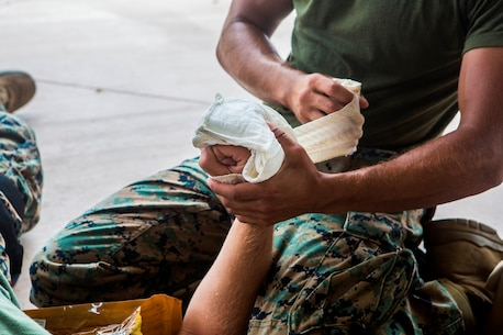 CAMP PENDLETON, Calif. – U.S. Marine Lance Cpl. Laine Fife, a marksmanship coach with the Marksmanship Training Unit, Headquarters Company, Headquarters Regiment, 1st Marine Logistics Group, uses gauze to wrap up a wounded hand during the practical application portion of a combat lifesaver course July 22, 2017. Through the CLS course, Marines add combat casualty care to their arsenal of individual capabilities. (U.S. Marine Corps Photo by Lance Cpl. Joseph Sorci)