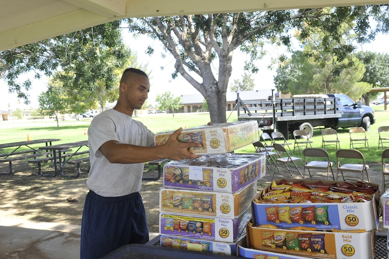 Airman 1st Class Archilious Green, 56th Component Maintenance Squadron fuels systems journeyman, stacks boxes of chips for the Back-to-School Bash July26, 2017 at Luke Air Force Base, Ariz. The event is being held from 5:30 p.m. until 8:00 p.m.