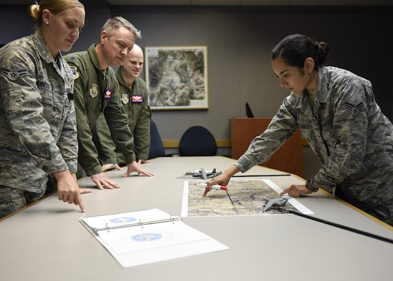 Senior Airman Brittany Fuentes, a collection requirements manager at Air Mobility Command, briefs information regarding a mobility mission to other anylysts July 18, 2017. (U.S. Air Force photo by Staff Sgt. Stephenie Wade)