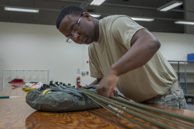Tech. Sgt. Johnnie Sims, 403rd Operations Support Squadron Aircrew Flight Equipment technician, at Keesler Air Force Base, Mississippi, packs a parachute during a 374 OSS manning assist, July 20, 2017, at Yokota Air Base, Japan. Sims assists 374 OSS with Yokota's transition from C-130H Hercules to C-130J Super Hercules. (U.S. Air Force photo by Airman 1st Class Juan Torres)