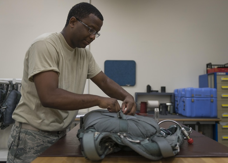 Tech. Sgt. Johnnie Sims, 403rd Operations Support Squadron Aircrew Flight Equipment technician, at Keesler Air Force Base, Mississippi, finishes packing a parachute, July 20, 2017, at Yokota Air Base, Japan. Sims assists 374 OSS with Yokota's transition from C-130H Hercules to C-130J Super Hercules. (U.S. Air Force photo by Airman 1st Class Juan Torres)