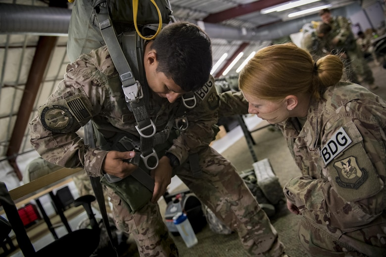 Staff Sgt. Luis Dominguez and Senior Airman Jenny Walker, 823d Base Defense Squadron close precision engagement team members, ensure Dominguez's gear is equipped properly, July 21, 2017, at Moody Air Force Base, Ga. This training was in preparation for an upcoming mission readiness exercise where airmen serve as an airborne advanced team, with the mission to create an initial presence and clear a path for follow-on forces to arrive on scene. (U.S. Air Force photo by Airman 1st Class Daniel Snider)