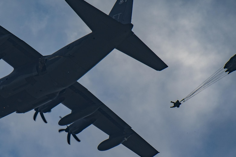 A member of the 823d Base Defense Squadron drops from an HC-130J Combat King II as his parachute catches wind, July 21, 2017, at the Lee Fulp Drop Zone in Tifton, Ga. This training was in preparation for an upcoming mission readiness exercise where airmen serve as an airborne advanced team, with the mission to create an initial presence and clear a path for follow-on forces to arrive on scene. (U.S. Air Force photo by Airman 1st Class Daniel Snider)