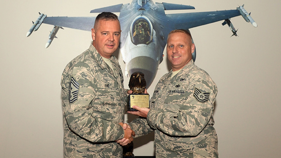 1st Air Force Command Chief Master Sgt. Richard King presents Tech. Sgt. Gabriel Armstrong with the award for the Continental NORAD Region Aerospace Control Alert Command Post Controller of the Year on July 26, 2017, in Egg Harbor Township, N.J.  King presented Armstrong with this award for outstanding execution of the Aerospace Control Alert Mission. (U.S. Air National Guard photo by Airman 1st Class Cristina J. Allen/Released)