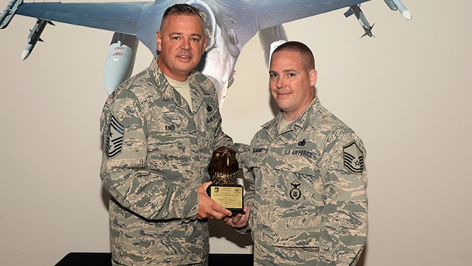 A picture of U.S. Air Force 1st Air Force Command Chief Master Sgt. Richard King presenting Master Sgt. Kevin Allman with the award for the Continental NORAD Region Aerospace Control Alert Security Forces Member of the Year.