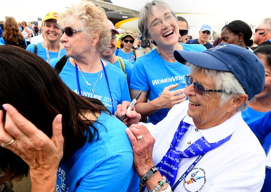 Secretary of the Air Force Heather Wilson laughs with Women's Auxiliary Service Pilot Jane Doyle while she autographs a T-shirt following a group portrait of women aviators in Oshkosh, Wisc., July 26, 2017. (U.S. Air Force photo/Scott M. Ash)