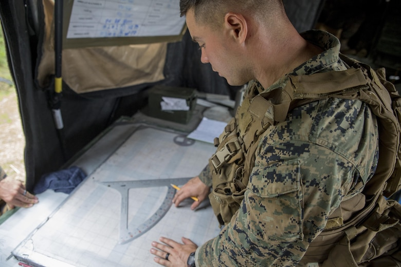A Marine plots call-for-fire coordinates during a live-fire range at Camp Lejeune, N.C., July 26, 2017. The purpose of this field operation is to test and improve the unit's capabilities by putting the Marines into a simulated combat environment. The Marine is with 1st Battalion, 10th Marine Regiment. (U.S. Marine Corps photo by Lance Cpl. Holly Pernell)
